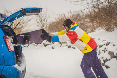 The snowboard does not fit into the car. A snowboarder is trying to stick a snowboard into a car. Humor, fun