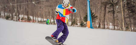 Young man jumping with a snowboard in the mountains BANNER, LONG FORMAT