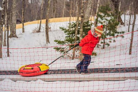 Boy with tubing rises on a travelator to the mountain. Child having fun on snow tube. Boy is riding a tubing. Winter fun for children
