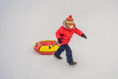 Child having fun on snow tube. Boy is riding a tubing. Winter fun for children Stock Photo