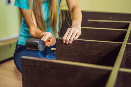 Caucasian woman using screwdriver for assembling furniture. Фото со стока