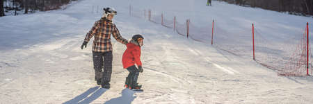 Mother teaches son snowboarding. Activities for children in winter. Childrens winter sport. Lifestyle BANNER, LONG FORMAT Stock Photo
