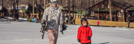 Dad teaches son snowboarding. Activities for children in winter. Childrens winter sport. Lifestyle BANNER, LONG FORMAT Stock Photo