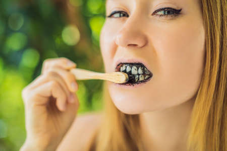 Young woman brush teeth using Activated charcoal powder for brushing and whitening teeth. Bamboo eco brush Stock fotó