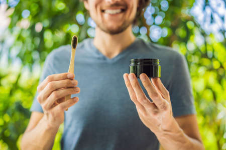 Young man brush teeth using Activated charcoal powder for brushing and whitening teeth. Bamboo eco brush
