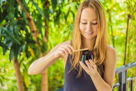 Young woman brush teeth using Activated charcoal powder for brushing and whitening teeth. Bamboo eco brush Stock Photo