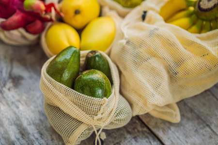 Fruit in a reusable bag on a stylish wooden kitchen surface. Zero waste concept, plastic free concept. Healthy clean eating diet and detox. Summer fruits.