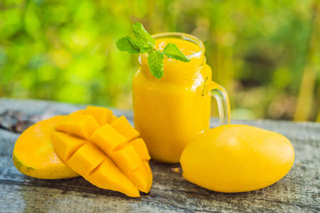 Mango smoothie in a glass Mason jar and mango on the old wooden background. Mango shake. Tropical fruit concept