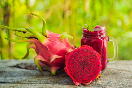 Dragon fruit smoothie on a wooden background.