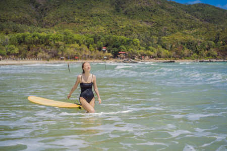 Beautiful young woman ride wave. Sporty surfer woman surfing on the background of blue sky, clouds and transparent waves. Outdoor Active.