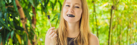 Young woman brush teeth using Activated charcoal powder for brushing and whitening teeth. Bamboo eco brush BANNER, LONG FORMAT Stock Photo