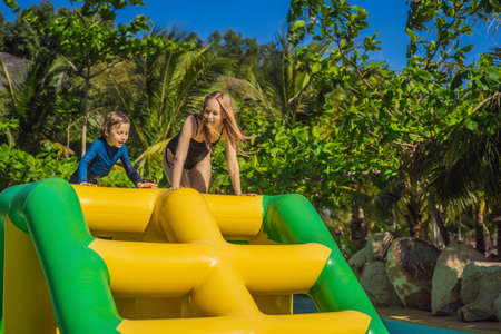 Mother and son go through an inflatable obstacle course in the pool