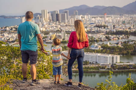 Happy family tourists on the background of Nha Trang city. Travel to Vietnam with kids Concept