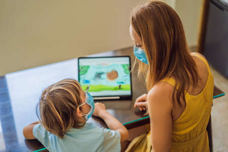 Boy studying online at home using a tablet. Mom helps him learn. Mom and son in medical masks to protect against coronovirus. Studying during quarantine. Global pandemic covid19 virus