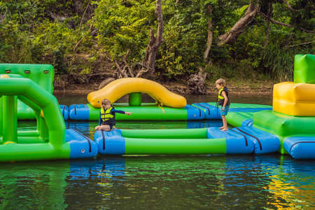Two boy runs an inflatable obstacle course In the lake 写真素材