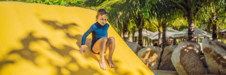 Cute boy runs an inflatable obstacle course in the pool BANNER, LONG FORMAT