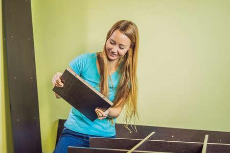 Caucasian woman using screwdriver for assembling furniture