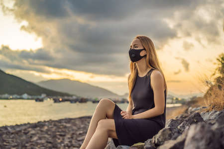 Self-isolation in nature. Young woman in Fashionable black medical mask with filter sitting by the river. Coronavirus 2019-ncov epidemic concept. Woman in a black medical mask. Portrait of a woman with expressive eyes during a virus or disease epidemic of Coronovirus