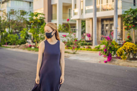 Fashionable black medical mask with filter in the city. Coronavirus 2019-ncov epidemic concept. Woman in a black medical mask. Portrait of a woman with expressive eyes during a virus or disease epidemic of Coronovirus Banco de Imagens