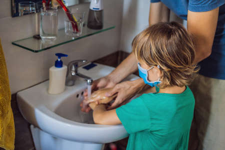 Dad teaches his son to wash his hands properly. Dad and son in medical masks because of coronovirus. Epidemic. Stay home. Wash your hands
