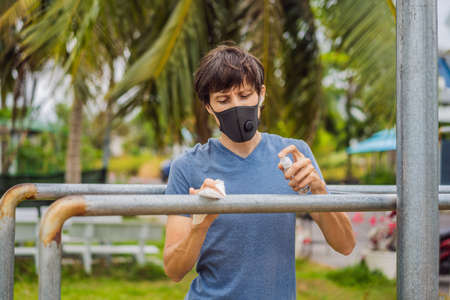 Man disinfects horizontal bar before sports. A man in a medical mask plays sports during the coronavirus epidemic