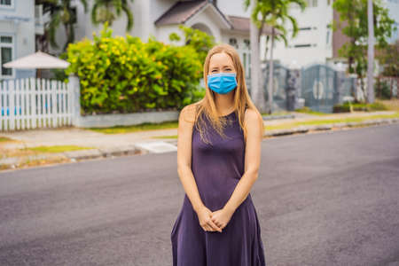 Woman in a small town in a medical mask because of a coronovirus epidemic Imagens