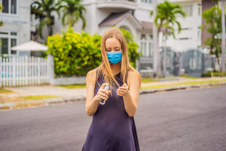 Woman in a small town in a medical mask uses a sanitizer because of a coronovirus epidemic 免版税图像 - 145512161