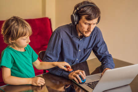 Man is trying to work from home because of the coronovirus epidemic, but his son is stopping him. Self-isolation at home. Children at home schooling. Parents at remote work. Quarantine, self-isolation, coronavirus
