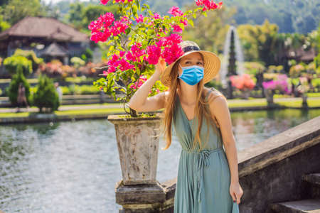 Young woman in medical mask tourist in Taman Tirtagangga, Water palace, Water park, Bali Indonesia Tourists fear the 2019-ncov virus. Medical masked tourists