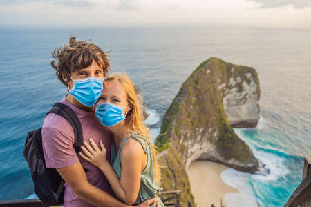 Family vacation lifestyle. Happy couple - man and woman in medical mask stand at viewpoint. Look at beautiful beach under high cliff. Travel destination in Bali. Popular place to visit on Nusa Penida island Tourists fear the 2019-ncov virus. Medical masked tourists