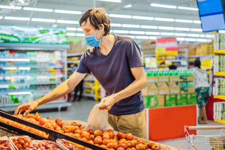 Man chooses tomatoes in a supermarket without using a plastic bag. Reusable bag for buying vegetables. Zero waste concept