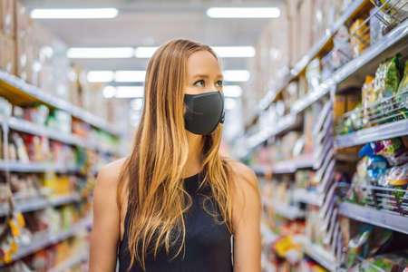 Alarmed female wears medical mask against coronavirus while grocery shopping in supermarket or store- health, safety and pandemic concept - young woman wearing protective mask and stockpiling food Banco de Imagens