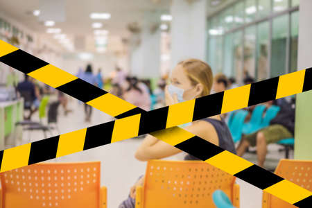 Young woman sitting in hospital waiting for a doctor's appointment. Patients In Doctors Waiting Room. Covid-19 quarantine yellow tape. Coronavirus or 2019-nCov virus