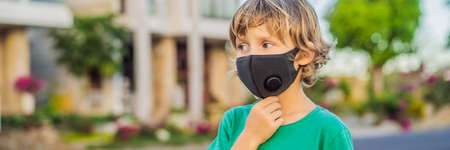 Fashionable black medical mask with filter in the city. Coronavirus 2019-ncov epidemic concept. Boy in a black medical mask. Portrait of a man with expressive eyes during a virus or disease epidemic of Coronovirus BANNER, LONG FORMAT