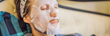 Young man doing facial mask sheet. Beauty and Skin Care Concept BANNER, LONG FORMAT Banco de Imagens