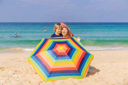 Coronavirus is over. Quarantine weakened. Take off the mask. Now you can go to public places. Mother and son on the beach in a hat and beach umbrella
