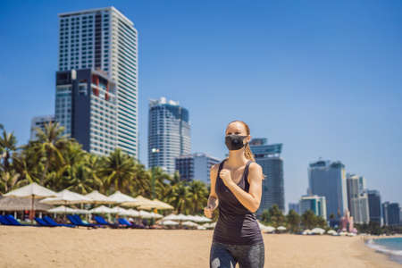 Woman runner wearing medical mask. Running in the city against the backdrop of the city. Coronavirus pandemic Covid-19. Sport, Active life in quarantine surgical sterilizing face mask protection. Outdoor run on athletics track in Corona Outbreak Banco de Imagens