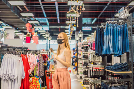 Woman in a clothing store in a medical mask because of a coronovirus. Quarantine is over, now you can go to the clothing store Imagens