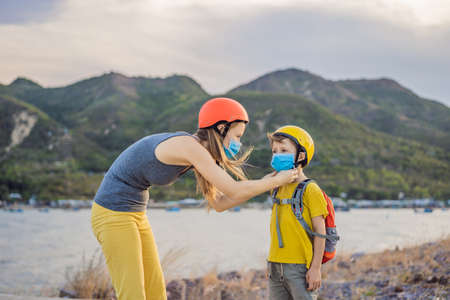 Active school kid boy and his mom in medical mask and safety helmet riding a bike with backpack on sunny day. Happy child biking on way to school. You need to go to school in a mask because of the coronavirus epidemic