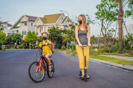 Active school kid boy and his mom in medical mask riding a bike with backpack on sunny day. Happy child biking on way to school. You need to go to school in a mask because of the coronavirus epidemic