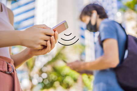 contact tracing app COVID-19 Pandemic Coronavirus Mobile Application - people Wearing Face Mask Using Smart Phone App in City Street to Aid Contact Tracing in Response to the 2019-20 Coronavirus Pandemic
