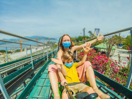 Mother and son in medical masks after the coronavirus epidemic on the alpine coaster