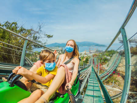 Mother and son in medical masks after the coronavirus epidemic on the alpine coaster Standard-Bild - 147948800