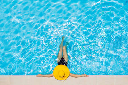 Woman sitting in a swimming pool in a large yellow sunhat Stok Fotoğraf