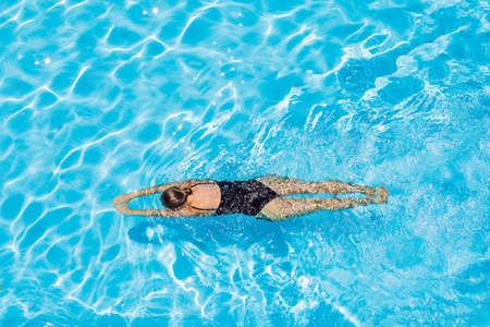 woman with black swimsuit swimming on a blue water pool
