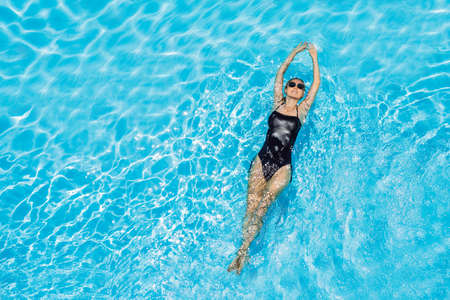 Woman in sunglasses swims in the pool