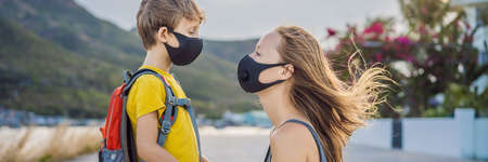 Mother puts her child a face protective mask on the street. Stop the infection. Coronavirus quarantine. Apocalypse. Health care concept. Mask against infectious diseases and flu
