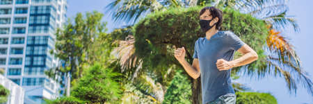 Man runner wearing medical mask. Running in the city against the backdrop of the city. Coronavirus pandemic Covid-19. Sport, Active life in quarantine surgical sterilizing face mask protection. Outdoor run on athletics track in Corona Outbreak