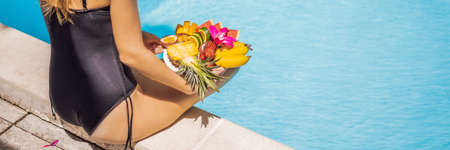 Young woman relaxing and eating fruit plate by the hotel pool. Exotic summer diet. Photo of legs with healthy food by the poolside, top view from above.