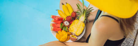 Young woman relaxing and eating fruit plate by the hotel pool. Exotic summer diet. Photo of legs with healthy food by the poolside, top view from above. Tropical beach lifestyle BANNER, LONG FORMAT